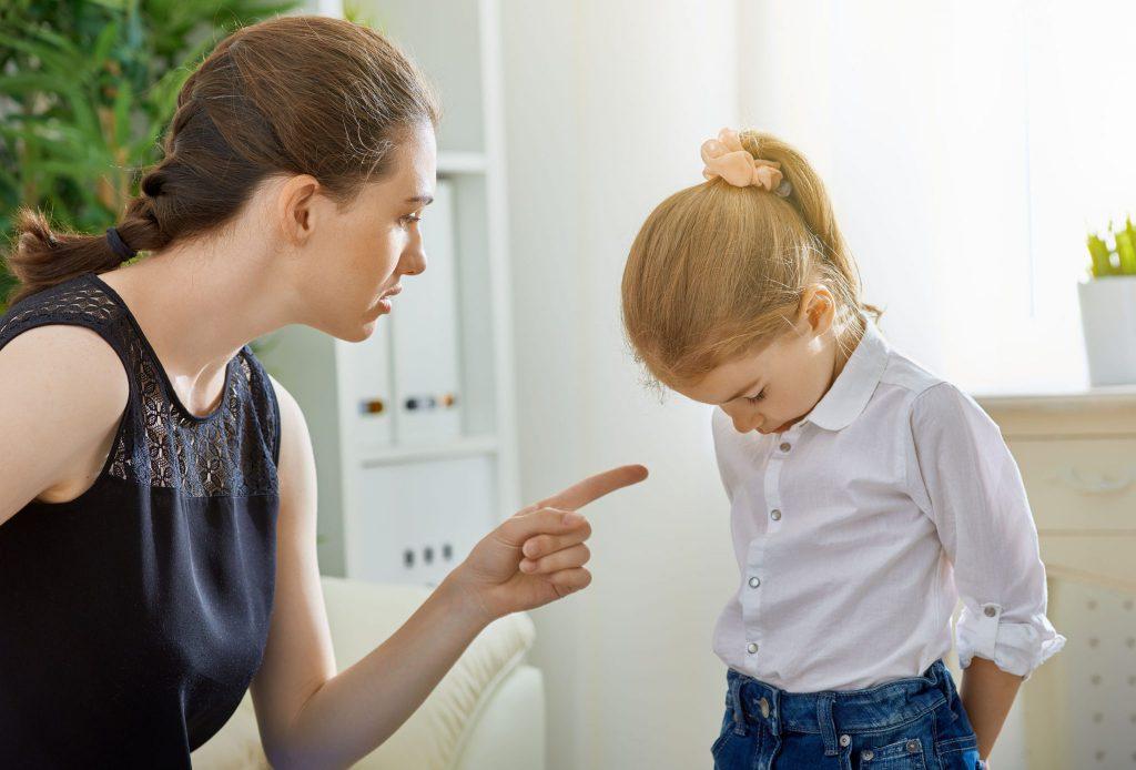 Mulher brava, falando com menina pequena enquanto aponta o dedo indicador esquerdo para ela. A menina está com a cabeça baixa e os olhos fechados.