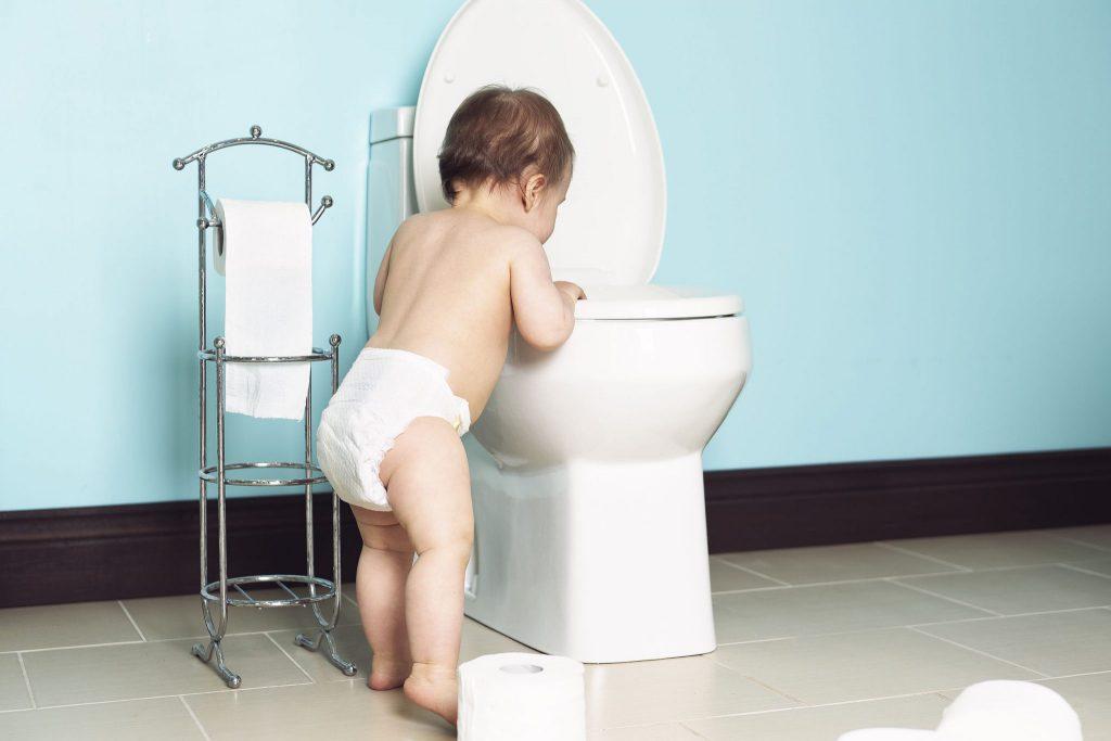 Bebê, usando fraldas, apoiado em uma privada, com as mãos no assento, e olhando para dentro dela.