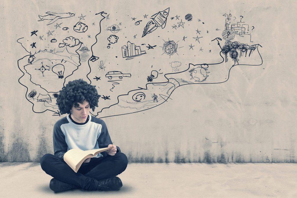 Menino sentado no chão com as pernas cruzadas, lendo um livro. Atrás dele, desenhos em uma parede branca, parecem que saem de sua cabeça.