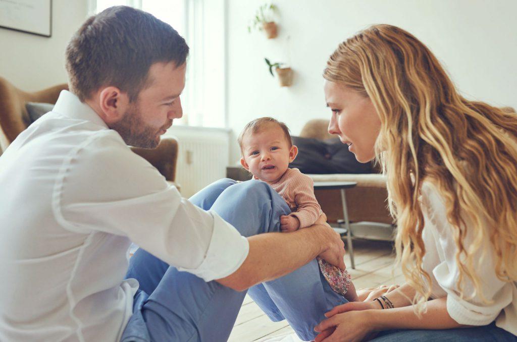 Homem segurando bebê pequena em suas pernas, e mulher ao seu lado, olhando para a pequena com expressão confusa.