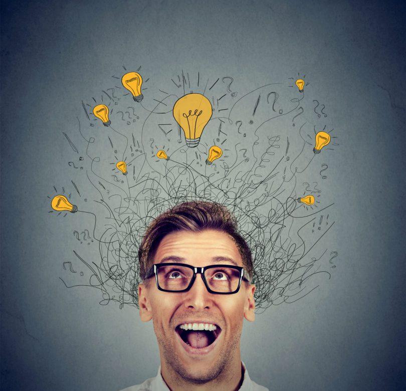 Homem usando óculos, com sua boca aberta, e desenhos flutuando sobre sua cabeça com fios e lâmpadas acesas.