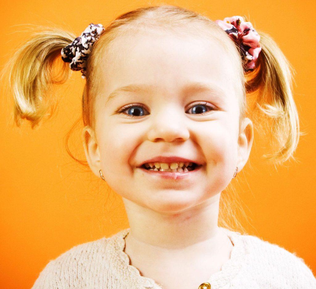 Menina pequena, com cabelos loiros presos em dois rabos laterais