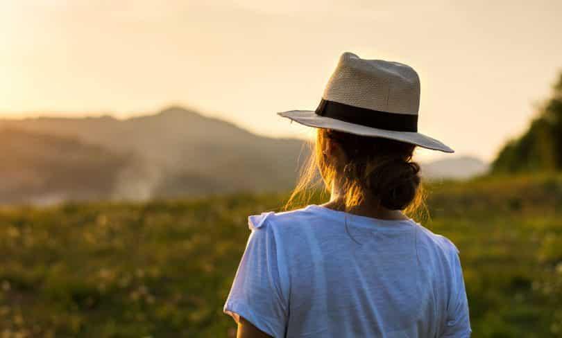 Mulher de chapéu apreciando a vista do pôr do sol sobre uma colina.