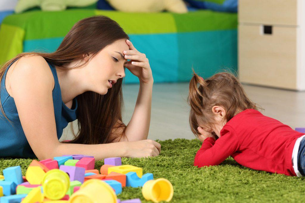 Mulher deitada em tapete de grama com menina pequena. A menina cobre seu rosto com as mãos, e a mulher tem uma de suas mãos na testa, com expressão de cansaço.