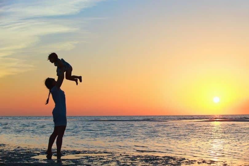 Mãe levantando filho na beira da praia