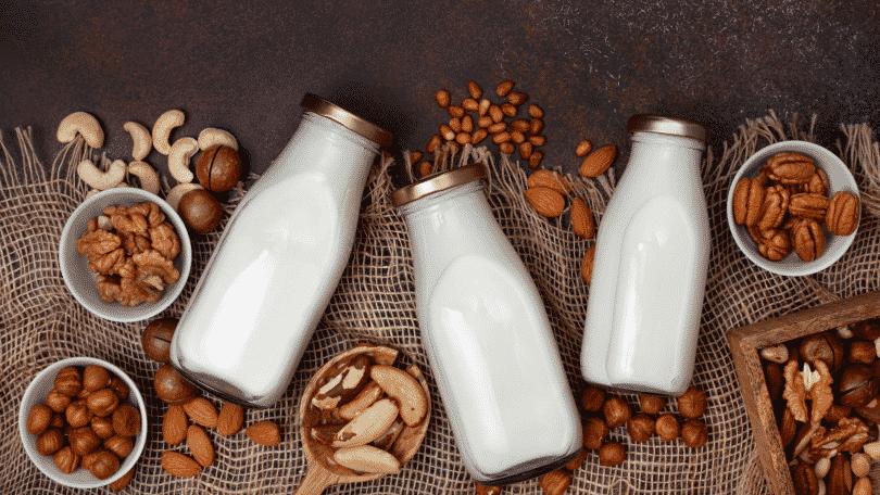 Sementes e castanhas em uma mesa e recipientes de vidro com leite