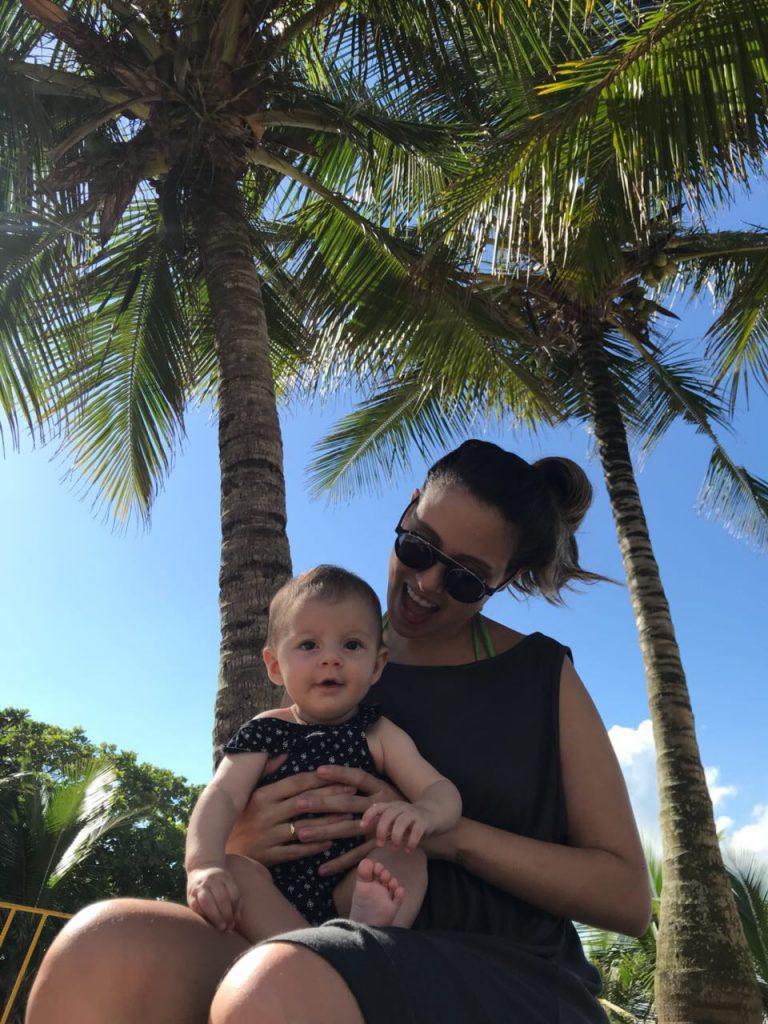 Mulher segurando bebê ao lado de coqueiros