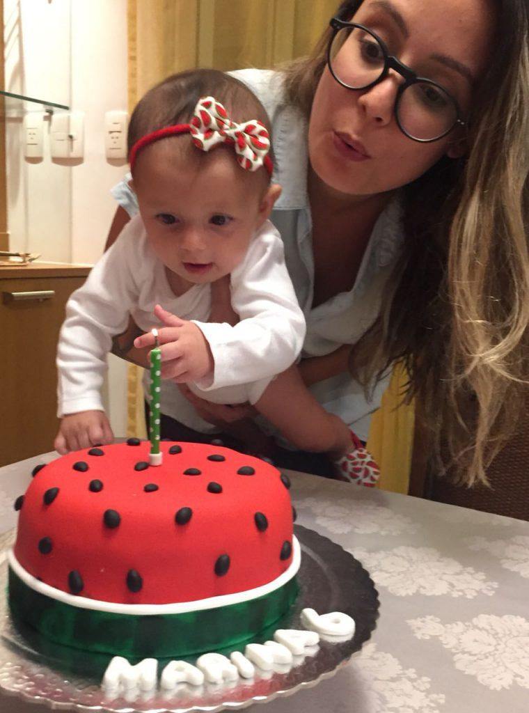Mulher segurando bebê em frente a um bolo de aniversário