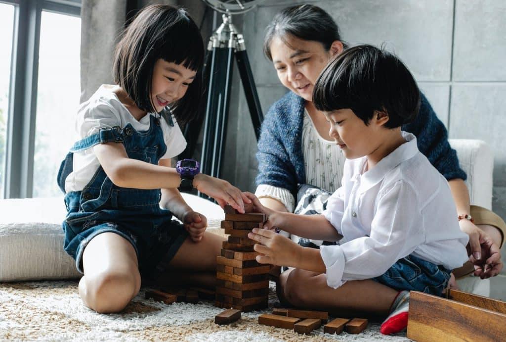 Mulher adulta brinca com crianças.