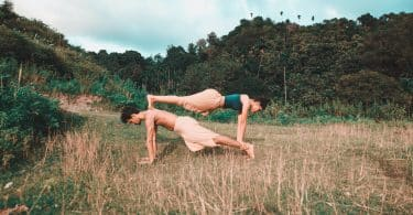 Homem e mulher em uma posição de yoga em um gramado