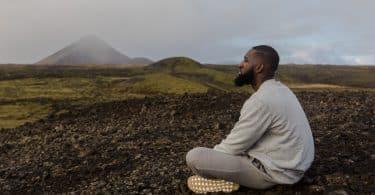 Homem sentado em um chão de terra olhando para o horizonte