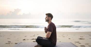 Homem sentado na areia de uma praia.