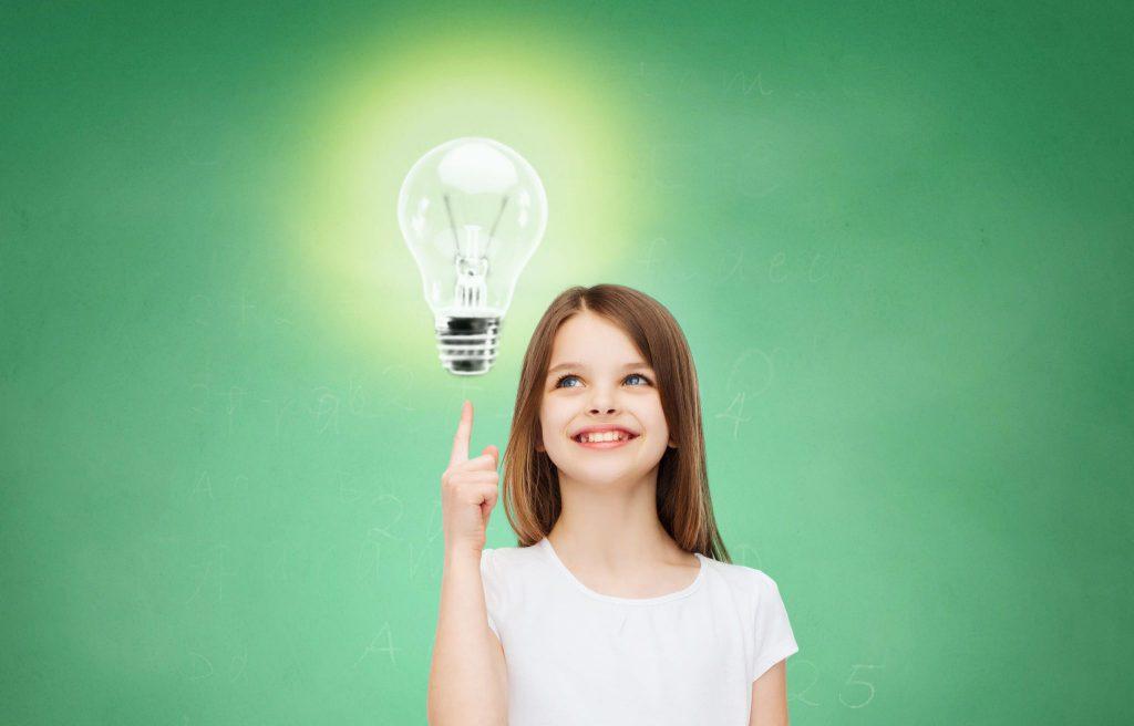 Menina com dedo para cima olhando para lâmpada acesa voando