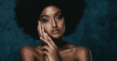 Imagem de uma modelo com uma mão no rosto, olhando para a câmera