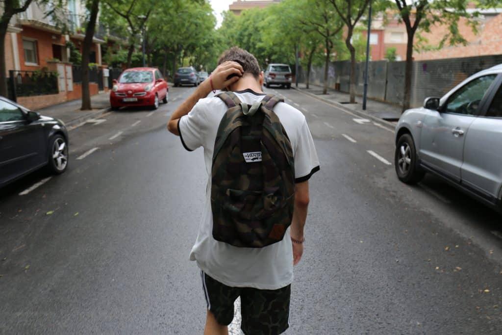 Adolescente andando no meio da rua com a mão na cabeça