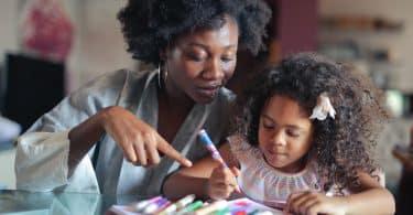 Criança pintando ao lado de uma mulher