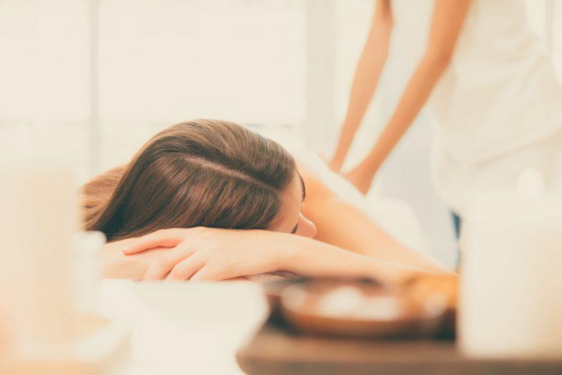 Mulher branca deitada recebendo massagem nas costas.