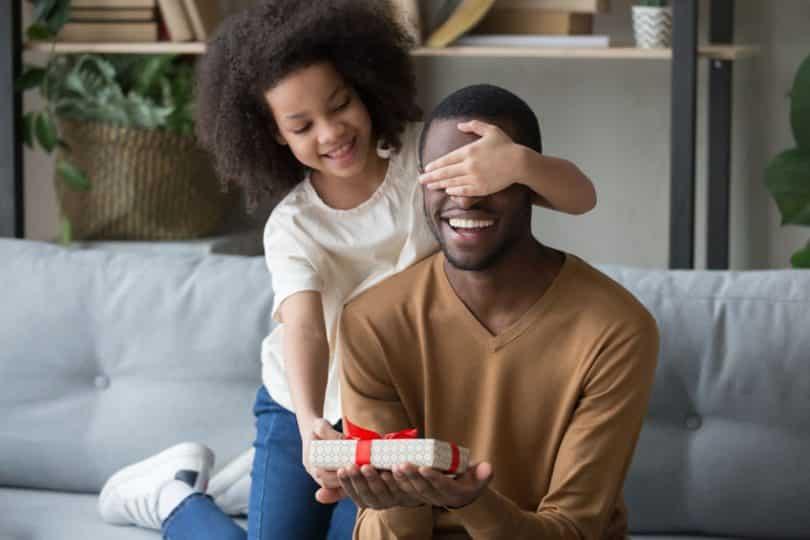 Garota tampando os olhos do pai e entregando presente em suas mãos