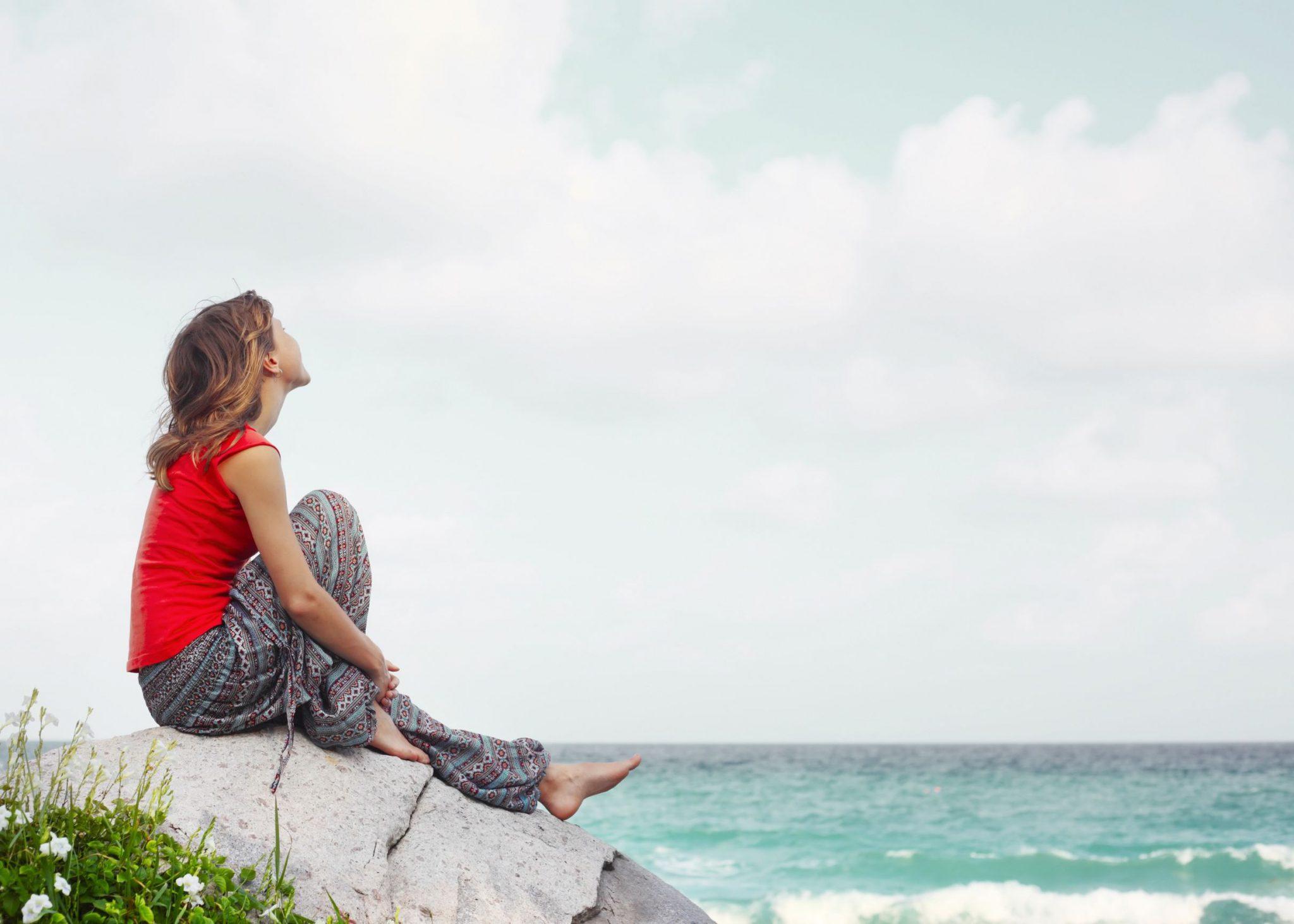 Moça loira de perfil, sentada em uma pedra da praia. Ela volta o rosto ao alto, o vento esvoaça os cabelos. Ao fundo, céu claro com nuvens e o mar agitado.