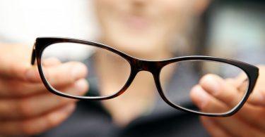 Foto em fundo desfocado: imagem de uma pessoa com discreto sorriso, do ombro para cima, segurando em primeiro plano, óculos com armação marrom. Fim da descrição.