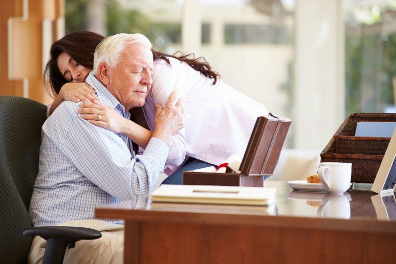 Foto de um pai abraçando sua filha.