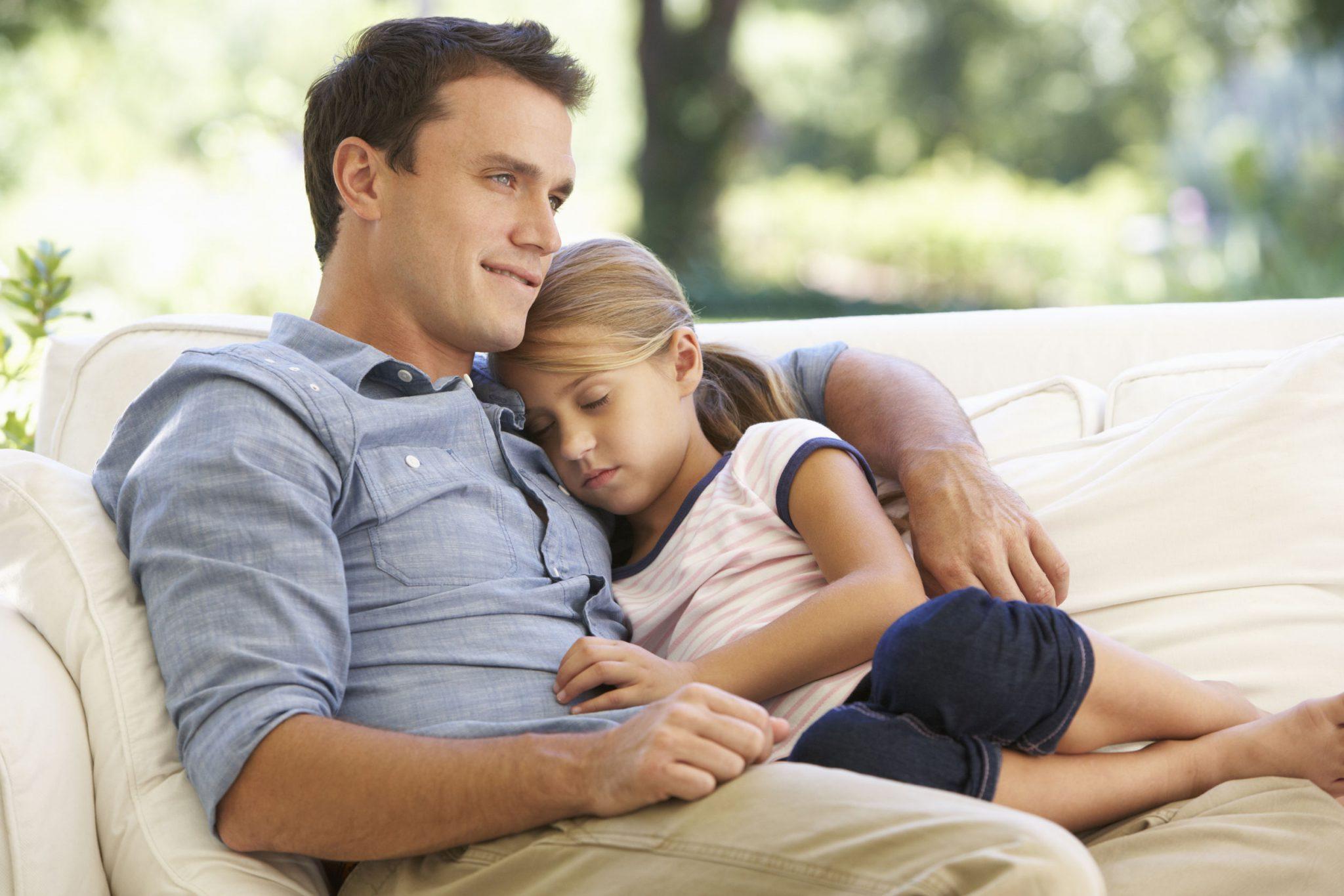 Foto com fundo desfocado de natureza. O jovem pai sorridente, sentado em um sofá branco, aconchega com o braço direito a filha de aproximadamente 7 anos, adormecida, encostada no peito paterno. Os dois são loiros e usam roupas informais de passeio.