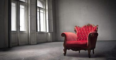 Foto de um amplo cômodo em cor cinza claro, com janelões à esquerda, por onde a luz adentra. Ao lado direito, apenas uma poltrona estilo Luiz XV em madeira entalhada, forrada em veludo vermelho gasto com encosto em capitonê.
