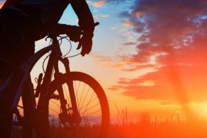Foto com fundo de natureza ao entardecer mostra o céu em tons de azul com nuvens escuras no topo até esmaecer em amarelo dourado abaixo. Ao lado esquerdo, silhueta parcial de uma pessoa em pé, com braços apoiados no guidão da bike.