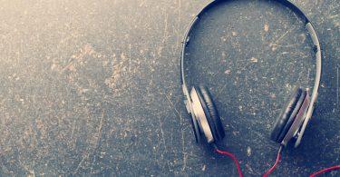 Foto em fundo de chão cimentado gasto. Ao lado direito, fones com fio vermelho.