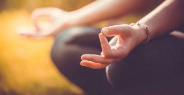 Foto em fundo desfocado amarelo mostra mãos apoiadas nos joelhos cobertos por calça legging preta. Com as palmas iluminadas voltadas acima, pontas dos dedos polegar e indicador tocam-se em JNANA MUDRA.