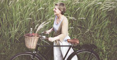 A foto mostra uma mulher sorridente, loira com cabelos curtos lisos e roupas claras leves. Ela está em pé, ao lado de uma bicicleta preta e segura com as duas mãos o guidão. Na cestinha da bicicleta, carrega frutas e uma garrafa. Ao fundo, o vento sopra e inclina a plantação que remete a trigo verde.