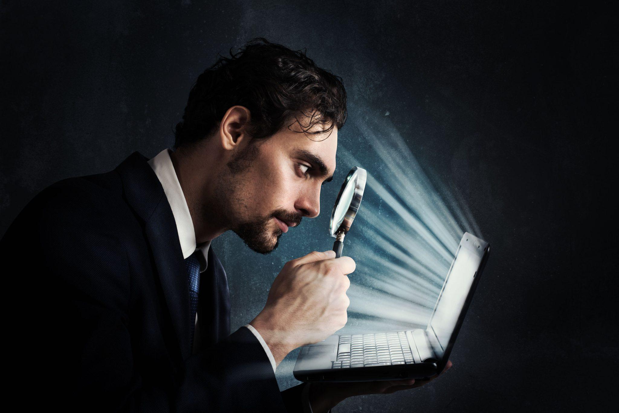 Foto em fundo preto mostra do peito para cima, um homem jovem de perfil à direita. Ele tem cabelos, sobrancelhas, bigode e cavanhaque escuros, usa roupa social preta. Na palma da mão esquerda apoia um laptop aberto, com a mão direita aproxima uma lupa à frente do rosto e foca os intensos raios luminosos emitidos pelo monitor. Fim da descrição