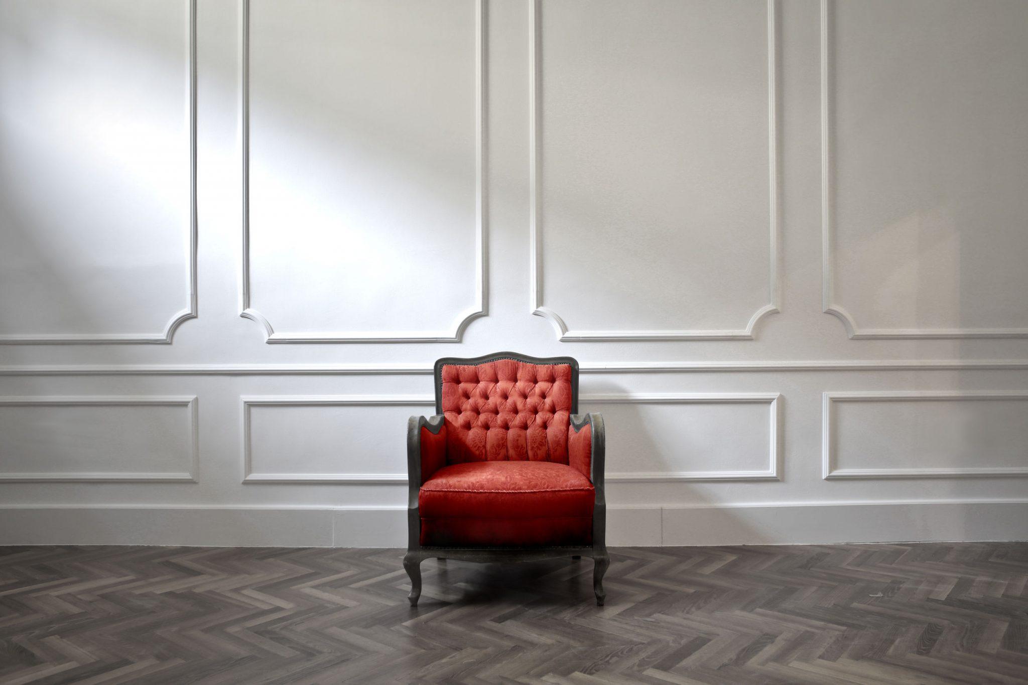 Foto. Ao centro, uma poltrona de madeira escura forrada com veludo vermelho, encostada junto à parede branca com molduras no mesmo tom. O chão de tacos claros e escuros, forma desenhos em zigue zague.