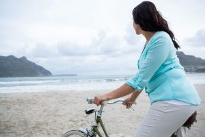 Foto de praia em dia nublado com céu de nuvens acinzentadas, montanhas nas extremidades e no mar poucas ondas. Em primeiro plano, imagem parcial de uma mulher morena sentada em uma bike, na areia. Ela olha ao fundo.