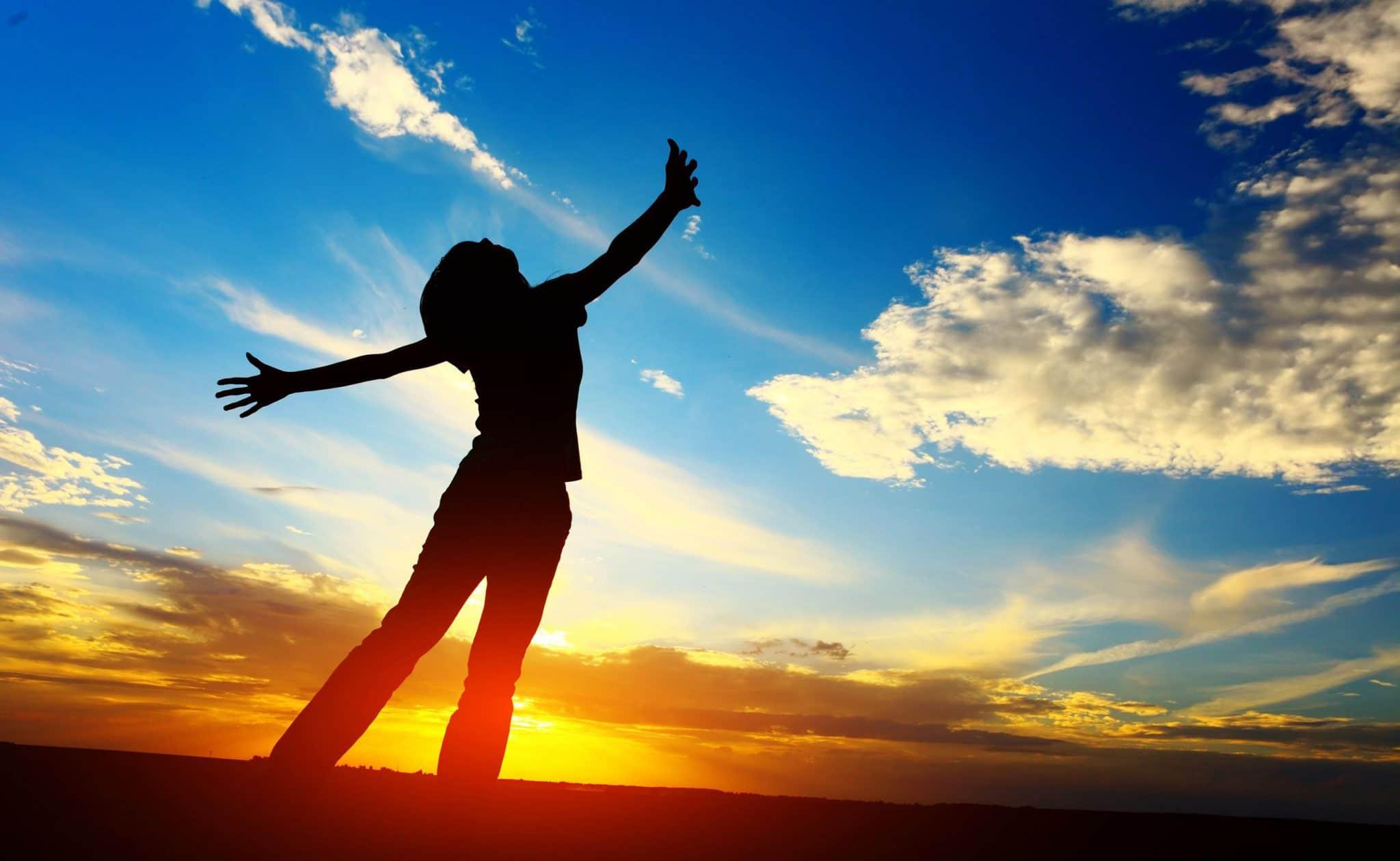 Silhueta de pessoa em pé, braços abertos em cruz, mãos espalmadas e cabeça voltada ao alto. Ao fundo, o céu com nuvens claras e o sol poente.