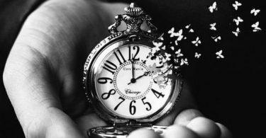 Mão, em preto e branco, segurando relógio que esta desmanchando em fragmentos que se transformam em pequenas borboletas.