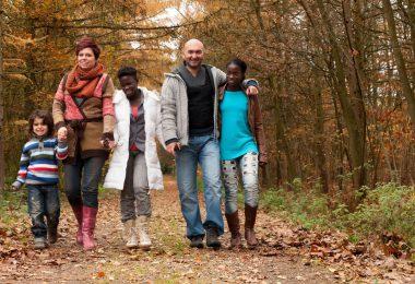 Família formada por um homem e mulher brancos, com 3 crianças negras, caminhando em meio a natureza.