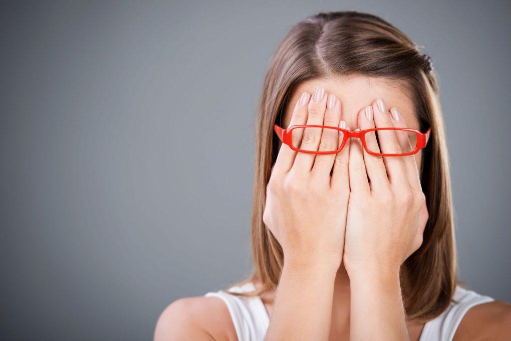 Mulher branca de cabelos castanhos e lisos com as mãos tampando os olhos e acima das mãos há um óculos retangular com a armação vermelha.