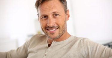 Homem com alguns cabelos grisalhos, barba rala e sorridente, sentado em sofá.