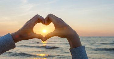 Mãos em formato de coração. Apontadas para o horizonte. Com o pôr do sol e o mar ao fundo.
