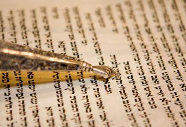 Papel envelhecido com escrituras em hebraico e por cima há um cabo fino e dourado que contém uma pequena mão também dourada que é utilizada para acompanhar a leitura do texto.