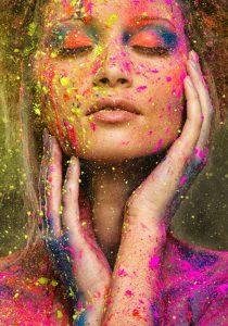 Mulher de olhos fechados, com as mãos tocando levemente o seu rosto. Ela está usando uma mistura de sombra laranja e azul nos olhos. Todo o seu rosto está manchado com respingos de tintas amarelas, azuis e rosas.