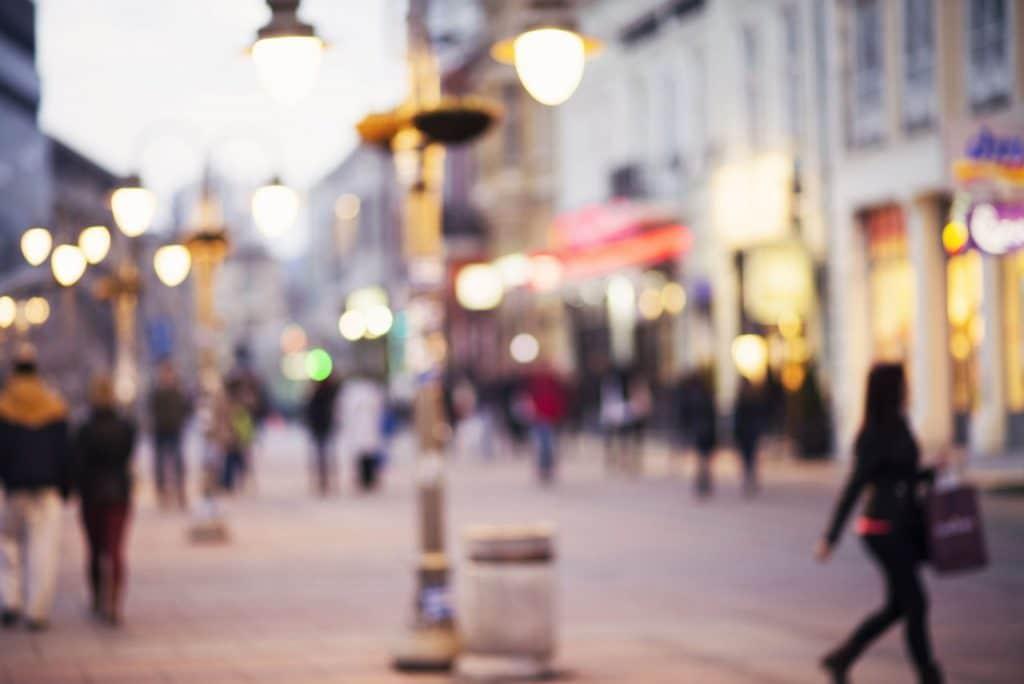 Foto de uma rua de uma cidade grande, com algumas pessoas passando com sacolas nas mãos e os postes de luz acesos.