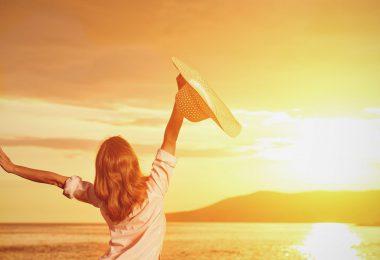Mulher sorridente com os braços abertos. Segurando chapéu. Olhando para o pôr do sol no mar.