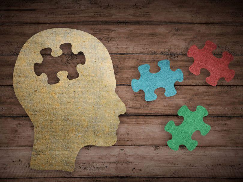 Desenho de uma cabeça humana com o meio faltando uma peça de quebra cabeça , cercada de outras peças de quebra cabeça coloridas , em cima de uma mesa de madeira.