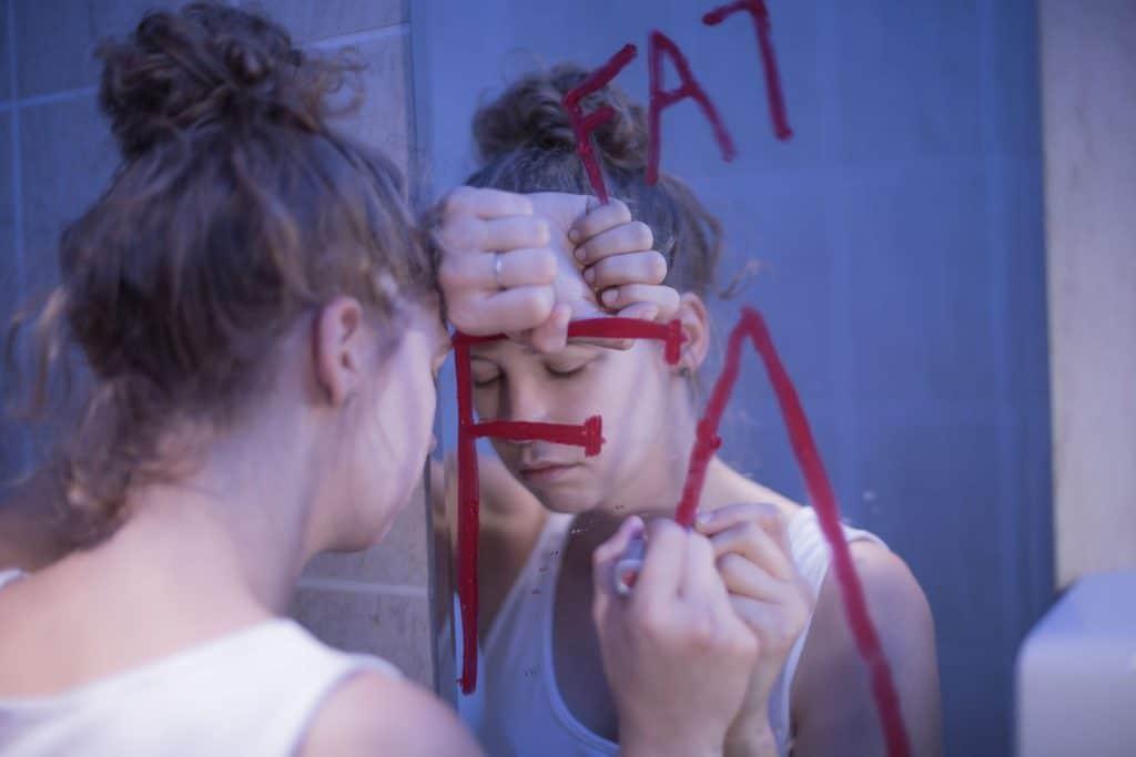 """Mulher branca com os cabelos presos em um coque apoiando a cabeça sobre o braço em frente a um espelho. A mulher está com uma expressão triste e segura um batom vermelho em sua mão direita que foi utilizado para escrever a palavra """"fat"""" no espelho, que significa """"gordo"""" em inglês."""