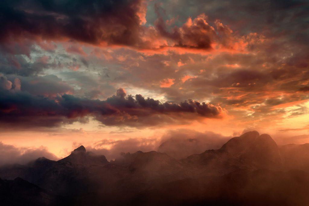 Uma paisagem com foco no céu que está alaranjado, porque é um final de tarde, e há muitas nuvens. Abaixo do céu é possível ver a silhueta de algumas montanhas.