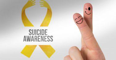 Fundo branco, fita amarela, legenda escrito conscientização do suicídio, com dois dedos cruzados com carinhas sorridentes nas pontas