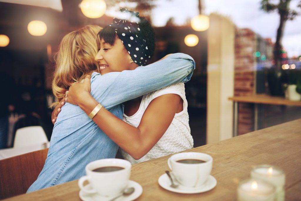Duas mulheres em um café se abraçando. Uma delas é loira e está vestindo uma camisa de manga longa azul clara e a outra é morena e está vestindo uma camiseta de manga curta branca, está com uma bandana preta com bolinhas brancas na cabeça e também está usando um bracelete dourado. Há também duas xícaras de café em cima de um balcão que está ao lado das duas moças.