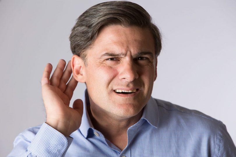 Homem em pé, com uma mão perto da orelha, como se não estivesse ouvindo.